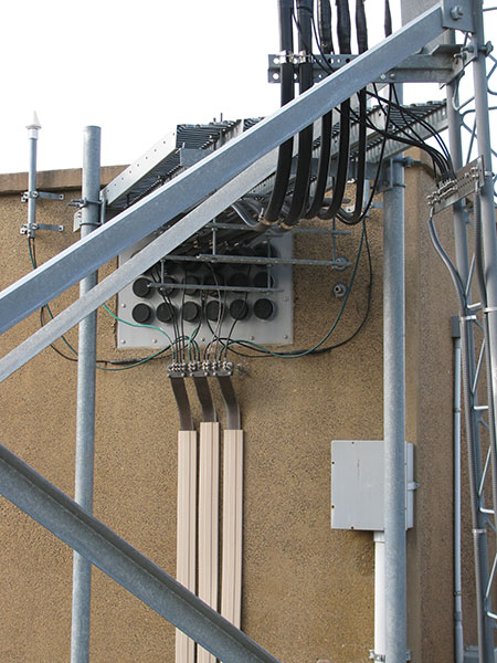 Figure 8. When lightning strikes one of the nine auxiliary sites that the county operates, energy is bled off the coax on the vertical run, the coax where it penetrates the firewall, and the interior side of the firewall.