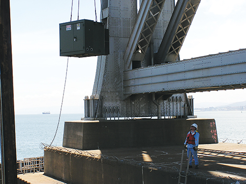 Photo 3. Landing the last medium voltage transformer at the base of the existing SFO Bay Bridge (E2) for temporary construction power. The challenge here was coordination with the tugboats, barge, crane operator and pile bucks.