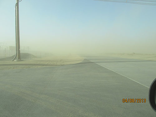 Photo 1B. Dust migrating off the site creates limited sight distance for drivers. The speed limit along this highway is 55 MPH.