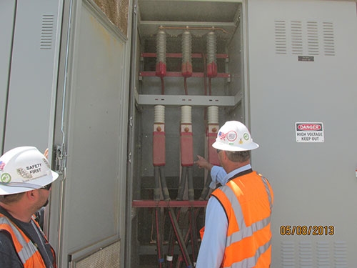 Photo 4A. Operators identifying major amounts of sand & dust that have migrated into the 35 kV breaker cubicles.