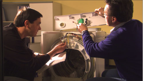 Initial Review. A UL product engineer and reviewing engineer evaluate the construction of a clothes dryer during their preliminary review of the product for compliance with the safety standard.