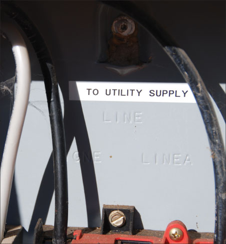 "Photo 6. Note the factory embossed ""LINE"" marking on this unfused ac disconnect (safety switch) just below the word ""UTILITY"" on the field-installed label. OK for backfeeding with the utility connection to the line terminals."